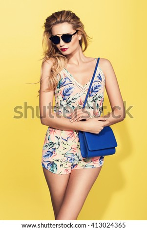 beautiful young blonde woman in nice summer clothes, posing on yellow background in studio. Fashion photo, handbag, high heels shoes - stock photo