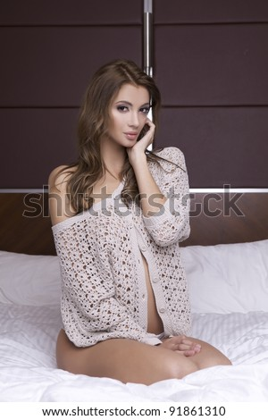 Beautiful young blonde woman in sweater on the bed - stock photo