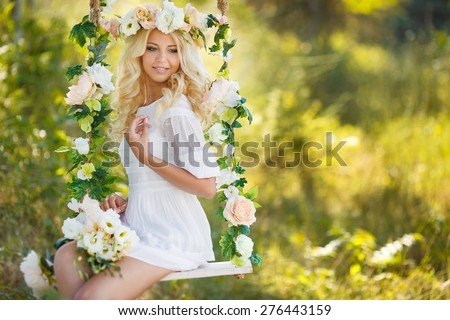 Beautiful young blonde woman in white dress and flower wreath with swing in summer outdoors.  - stock photo