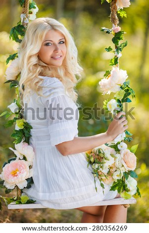 Beautiful young blonde woman in white dress and flower wreath with swing in summer outdoors. Woman outdoor. Summer portrait. Blonde girl in flowers.  - stock photo