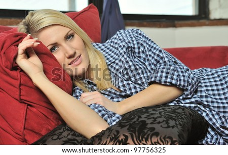 Beautiful young blonde woman lounging on red chaise lounge (chaise longue) chair wearing a men's shirt and on a black pillow - stock photo