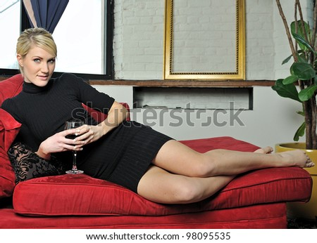 Beautiful young blonde woman lounging on red chaise lounge (chaise longue) in black dress and holding a glass of wine - stock photo
