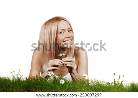 Beautiful young blonde woman lying on grass with chamomile flowers, isolated on white background - stock photo