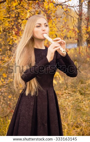 Beautiful young blonde woman playing flute recorder in autumn forest at sunset - stock photo