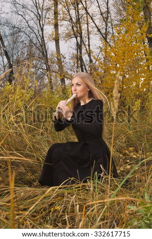 Beautiful young blonde woman playing flute recorder in autumn forest at sunset, opposing windy weather - stock photo