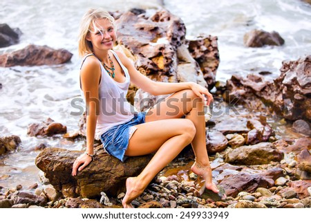 Beautiful young blonde woman posing outdoor at the rocky sea shore. Trendy fashion female model dressed in white top and denim sexy shorts - stock photo