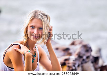 Beautiful young blonde woman posing outdoor at the rocky sea shore. Trendy fashion female model dressed in white top - stock photo