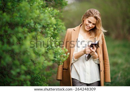 Beautiful young blonde  woman reading sms with smartphone outdoors in park  - stock photo