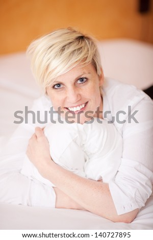 Beautiful young blonde woman relaxing in bed with a lovely big smile on her face - stock photo