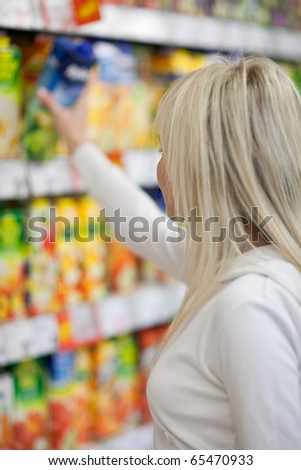 Beautiful young blonde woman shopping for fruit juices/soft-drinks/beverages in a grocery store/supermarket (shallow DOF; color toned image) - stock photo