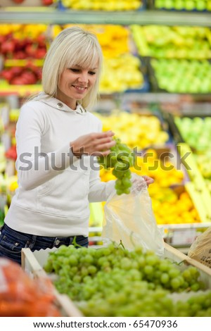 Beautiful young blonde woman shopping for fruits and vegetables in produce department of a grocery store/supermarket (shallow DOF; color toned image) - stock photo