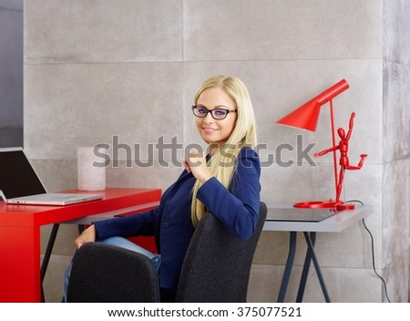 Beautiful young blonde woman sitting at desk, working with laptop computer, smiling at camera. - stock photo