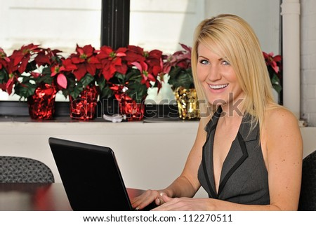Beautiful young blonde woman sitting in office working on computer at desk - smiling - stock photo
