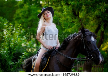 Beautiful young blonde woman sitting on a horse in white dress, in green garden.