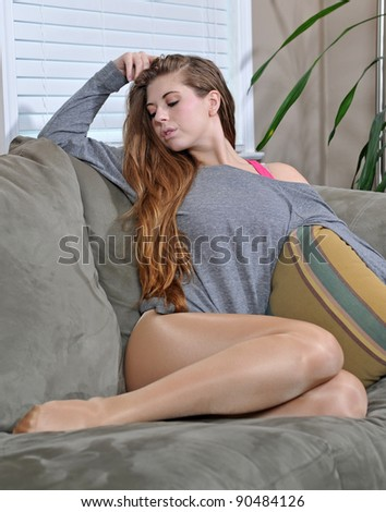 Beautiful young blonde woman sitting on couch in oversized grey t-shirt - pose - stock photo
