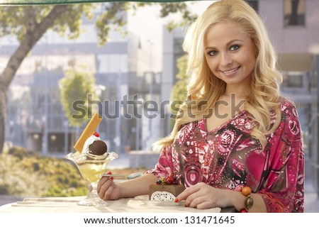 Beautiful young blonde woman smiling at outdoor cafe, having cake. - stock photo