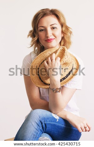 beautiful young blonde woman smiling while sitting with fashionable straw hat in hand, soft focus - stock photo