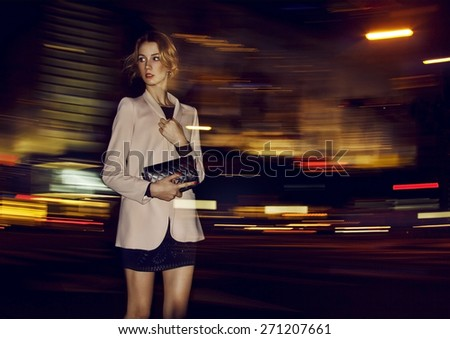 Beautiful young blonde woman walking in the dark night city, dressed in the skirt, jacket and with the handbag. Street lights around her in move. Developed from RAW. Retouched with special care. - stock photo