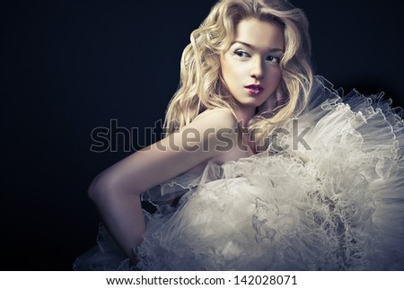 Beautiful young blonde woman wearing gorgeous dress standing over dark background - stock photo
