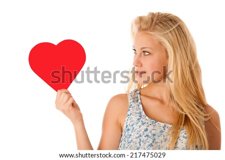 Beautiful young blonde woman with blue eyes holding red hart banner for valentines day isolated over white - stock photo