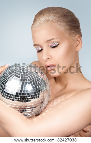 Beautiful young blonde woman with disco ball - stock photo