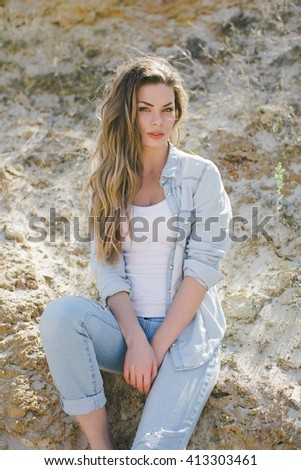 Beautiful young blonde woman with makeup in fashion clothes - stock photo