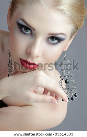 Beautiful young blonde woman with ornate earrings looking to camera studio shot - stock photo