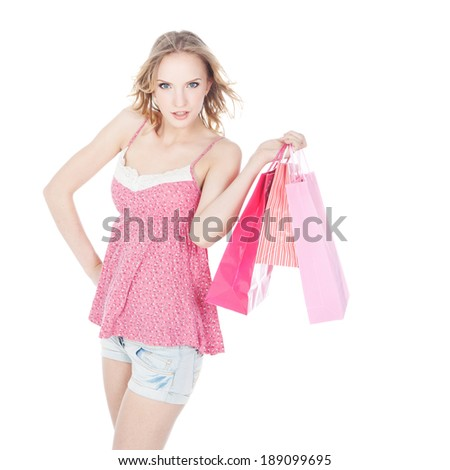 Beautiful young blonde woman with pink shopping bags over white background - stock photo