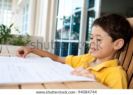 Beautiful young boy doing his homework at home - stock photo