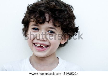 Beautiful young boy laughs as he shows his two missing teeth - stock photo