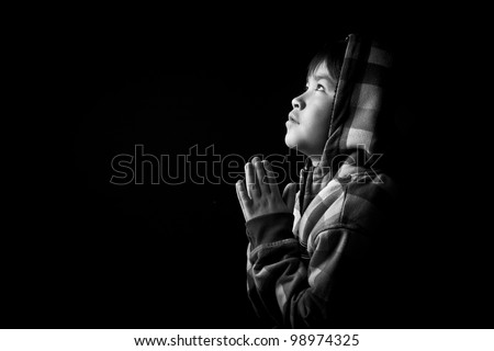 Beautiful young boy praying on black background in black and white - stock photo