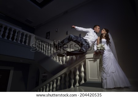 Beautiful young bride and groom kissing on stairs - stock photo