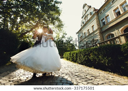 Beautiful young bride and handsome groom dancing outdoors near old mansion at sunset - stock photo