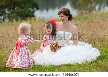 Beautiful young bride and little girl touching and gently gives a flower - stock photo