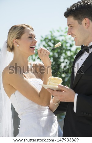 Beautiful young bride feeding wedding cake to groom outdoors - stock photo