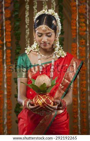 Beautiful young bride holding kalash - stock photo