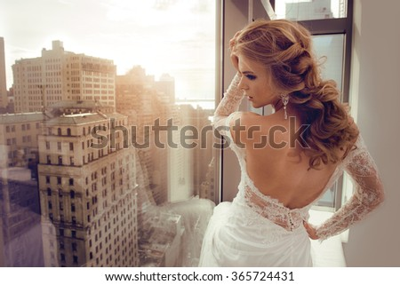 Beautiful Young bride in wedding dress posing near window - stock photo