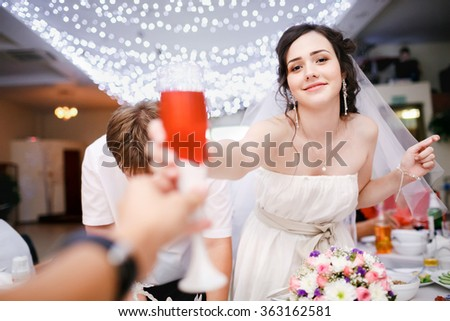 Beautiful young bride in white dress playfully raised a glass of champagne at wedding, and want to make a toast, clink glasses. Wedding banquet at a restaurant, ceiling garlands. Celebrating. Cheers. - stock photo