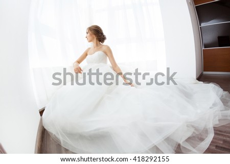 Beautiful young bride in white wedding dress indoors.  Luxuty model sitting against big window at home. Girl waiting her groom in bright room. Beautiful wedding hairdress. High key fisheye photo.