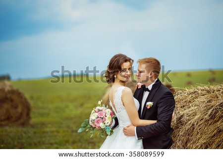Beautiful young bride is tenderly embracing husband at rural haystacks summer field background. - stock photo