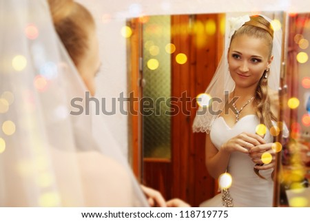Beautiful young bride looks in the mirror - stock photo