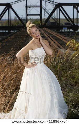Beautiful young bride modeling elegant bridal gown in rural field in front of rail bridge on sunny day.