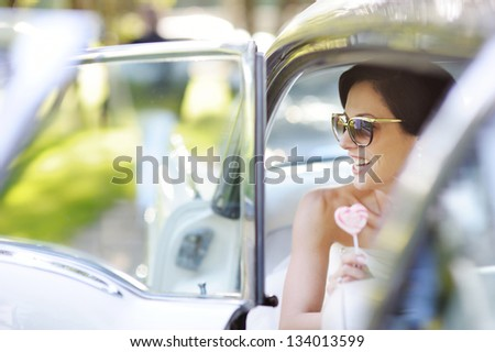 Beautiful young bride portrait in a car - stock photo