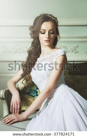 Beautiful Young Bride Sensualy Posing On Sofa. White Wedding Dress. Vintage interior. Attractive blonde bride closeup portrait - stock photo