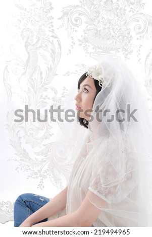 Beautiful young bride sitting on the floor in a wedding dress