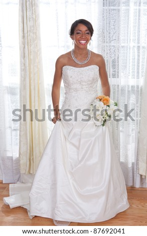 Beautiful Young Bride Standing by Window Smiling - stock photo