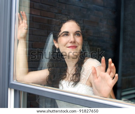 Beautiful young bride stares dreamily out of the window of her dressing room.  She has long dark curly hair and is wearing a veil and radiant glow. - stock photo