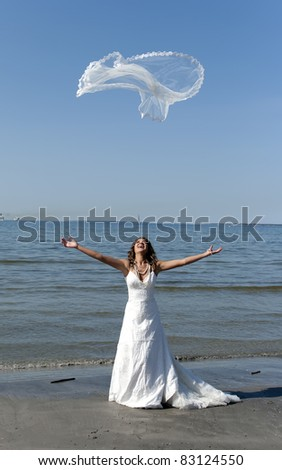 beautiful young bride throwing the veil near the sea