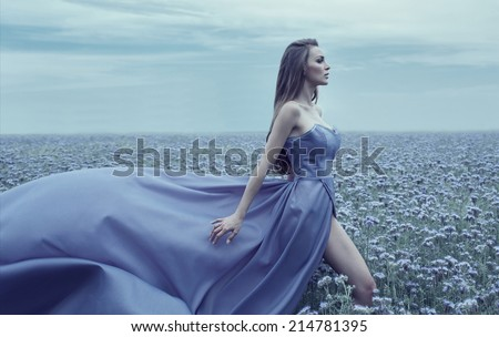 Beautiful young bride walking on the field of flowers - stock photo