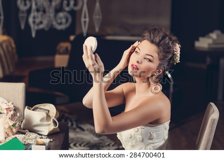 Beautiful young bride wearing fashion gown sitting on chair and looking into hand mirror - stock photo